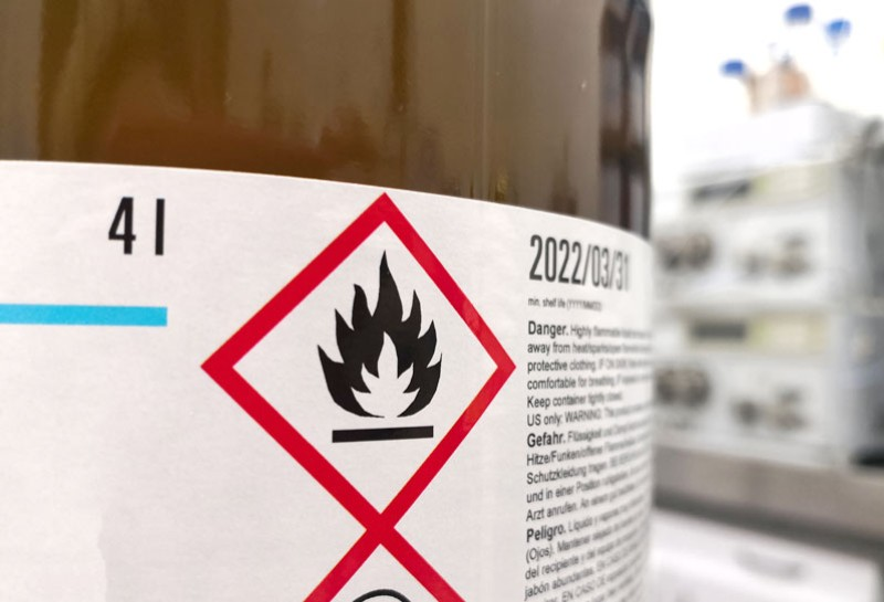 close up of a hazard and safety label on a brown bottle